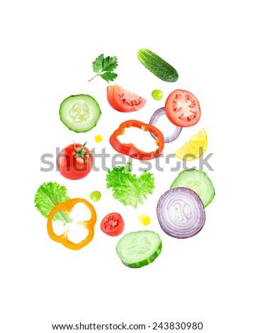 Falling fresh vegetable slices on white background - stock photo