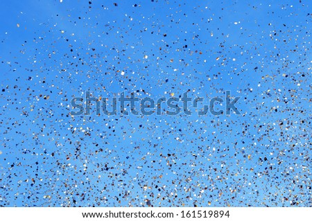 falling golden confetti in the city festival on blue sky background #3 - stock photo