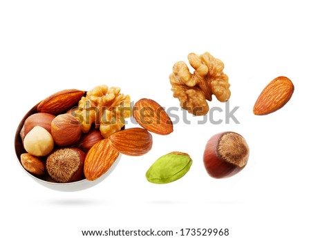 Falling nuts in bowl isolated on white background.