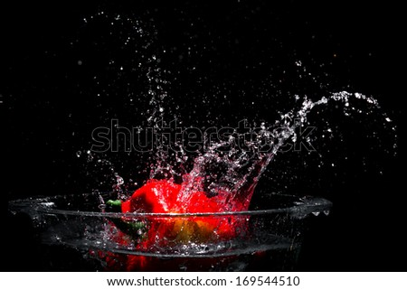 Falling red sweet pepper to tank with water - stock photo