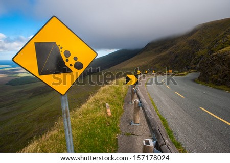 falling rocks Warning sign on a curvy road  - stock photo