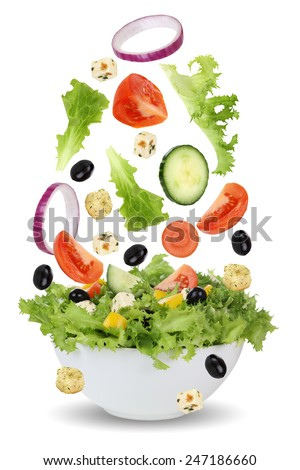 Falling salad in bowl with lettuce, tomatoes, Feta cheese, onion, olives and cucumber - stock photo