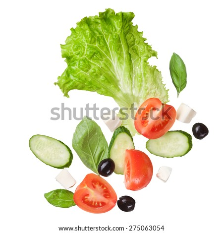falling salad isolated in white - red tomatoes, pepper, cheese, basil, cucumber and olives - stock photo