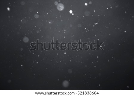 Falling snow on black background.