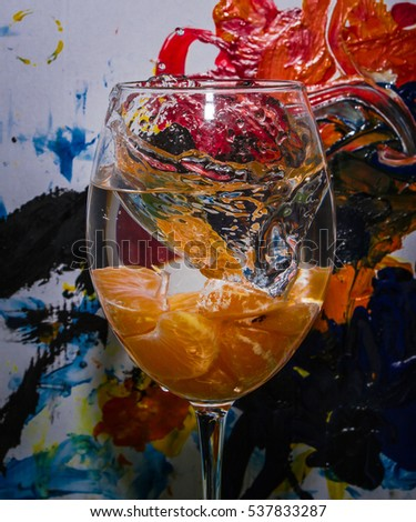 Falling tangerine in glass with splashes on abstract background