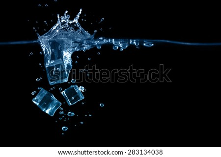 falling to the water ice cubes on dark background - stock photo