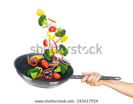 Falling vegetables in frying pan on an isolated white background - stock photo