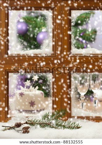 Falling winter snow onto pine cones and branch against a festive Christmas window, focus on pine cones and branch in front of window - stock photo