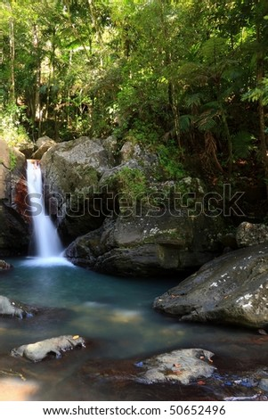 Falls and pool on La Mina River surrounded by the lush forest in  El Yunque rainforest in the Caribbean National Forest, Puerto Rico - stock photo