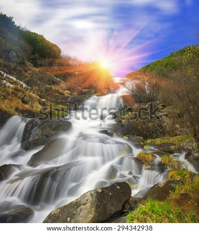 Falls breakers among melting snow under the peak of Hoverla, stormy clean water feeds the river Prut on the background of wild mountain slopes of the Carpathian Mountains. - stock photo