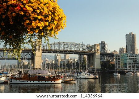 False Creek and Flower Basket, Vancouver. A False Creek view from Granville Island in Vancouver, British Columbia, Canada. The historic Burrard Bridge is in the background. - stock photo
