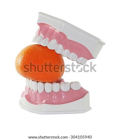 False teeth having a big bite into an orange  - stock photo