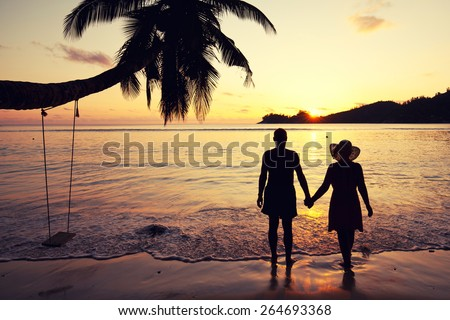 familiar couple in love holding hands at sunset at the seaside, seychelles beach - stock photo