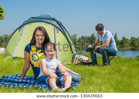 Families resting on the grass and camping with tent