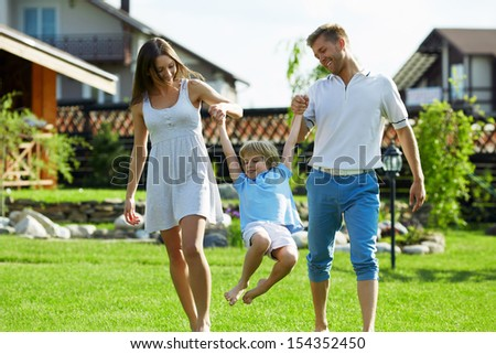 Families with a child on a lawn at the house - stock photo