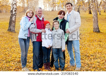 Families with children and grandparents in autumn park - stock photo