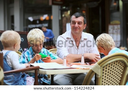 Family, a father with three children, two teenager twin sons and little cute baby girl, are having fun in cafe on summer terrace in a center of busy city street, boy is playing with smart phone - stock photo