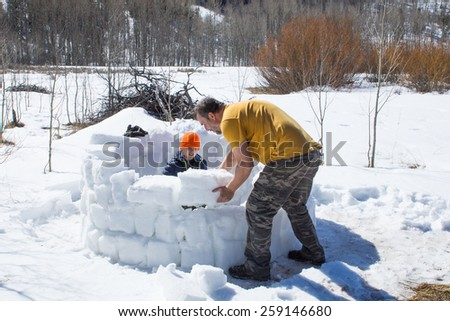 Family Activity: Construction of an Eskimo hut - the igloo from the bricks of dense snow - stock photo