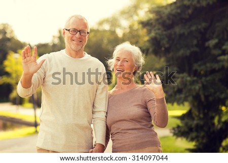 family, age, tourism, gesture and people concept - senior couple waving hands in city park - stock photo