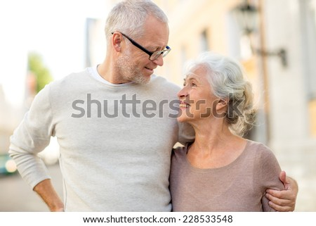 family, age, tourism, travel and people concept - senior couple hugging on city street - stock photo