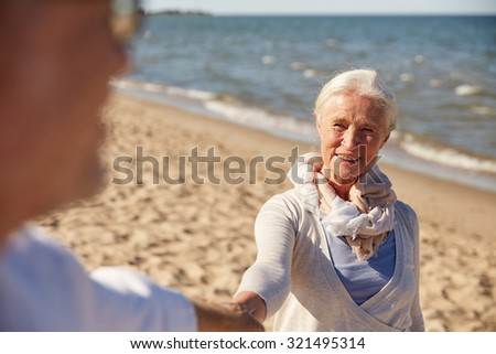family, age, travel, tourism and people concept - happy senior couple holding hands on summer beach - stock photo