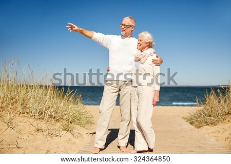 family, age, travel, tourism and people concept - happy senior couple pointing finger to something on summer beach - stock photo