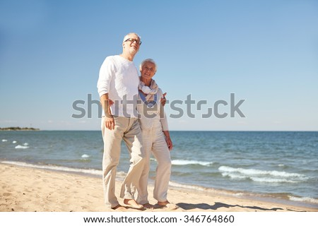 family, age, travel, tourism and people concept - happy senior couple walking along summer beach - stock photo