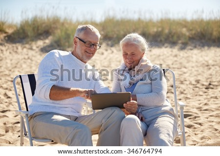 family, age, travel, tourism and people concept - happy senior couple with tablet pc computer resting in folding chairs on summer beach - stock photo