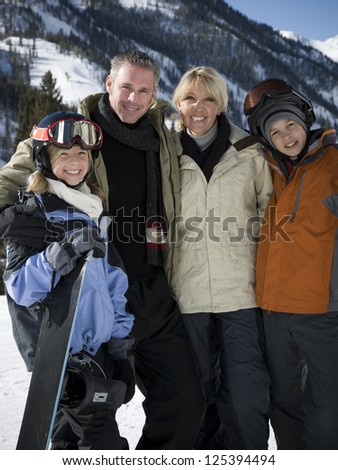 Family among the mountains in ski clothing - stock photo