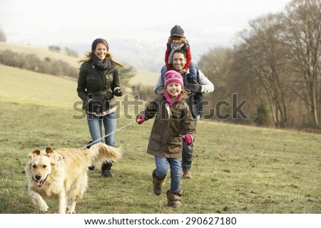 Family and dog on country walk in winter - stock photo