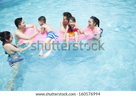 Family and friends playing in water at the pool - stock photo