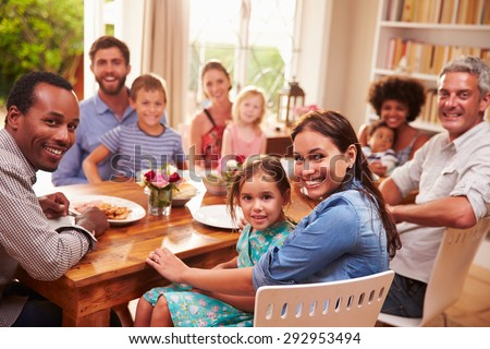 Family and friends sitting at a dining table, looking at camera - stock photo