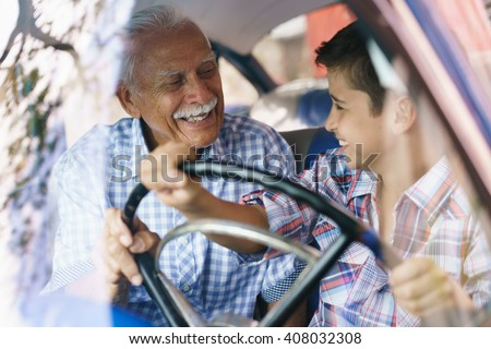 Family and Generation gap. Old grandpa spending time with his grandson and teaching him to drive. The boy holds the volante of a vintage car from the 60s. They both smile happy looking each other. - stock photo