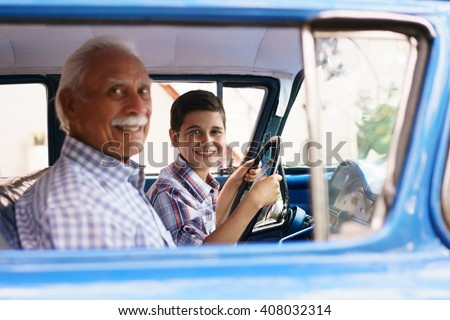 Family and Generation gap. Old grandpa spending time with his grandson. He teaches him to drive. The boy holds the volante of a vintage car from the 60s. They both smile happy looking at camera. - stock photo