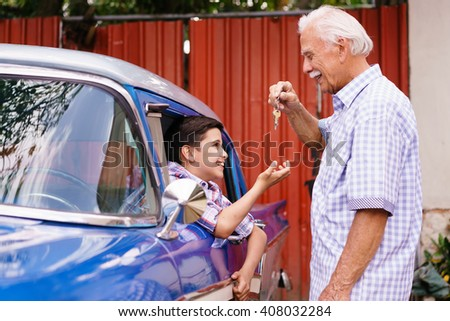Family and Generation gap. Old grandpa spending time with his grandson. The senior man gives the keys of a vintage car from the 60s to the preteen child sitting inside. They smile happy. - stock photo