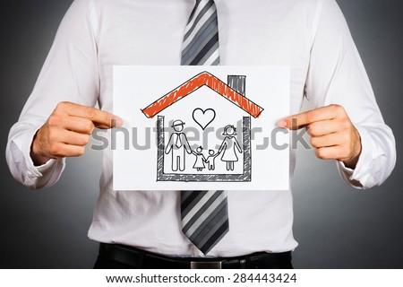 Family and home insurance concept. Businessman holding paper with drawing of a family, inside family home. - stock photo