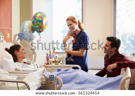 Family And Nurse With New Born Baby In Post Natal Department - stock photo
