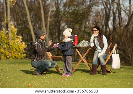 Family and picnic concepts. Young father teaching his daughter while mother sitting on woden chair and observing it. Happy family are on a picnic.
