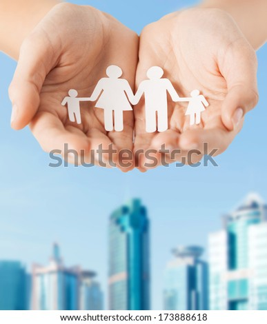 family and relations concept - close up of female cupped hands showing paper man family