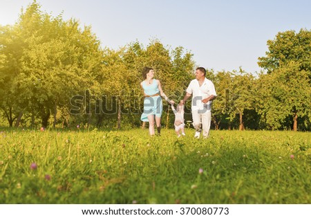 Family and Relationships Concepts. Happy Young Family Running Together Outdoors on Nature. Horizontal Image