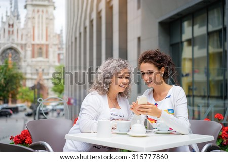 Family and technology. Aged woman and her adult daughter using smartphone at sidewalk cafe. - stock photo