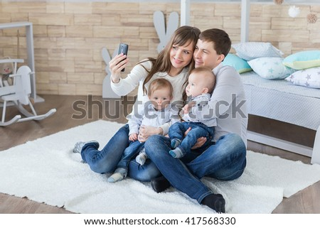 family and technology concept - happy parents and little boys twin taking selfie by smartphone in room - stock photo