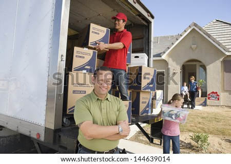 Family and worker unloading truck of cardboard boxes - stock photo