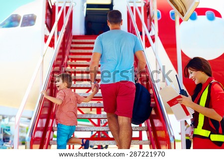 family are boarding on airplane, airhostess welcomes passengers - stock photo