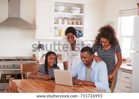 Family Around Kitchen Table Booking Vacation On Laptop Together