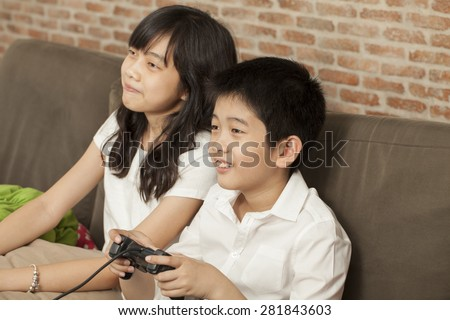 family, Asian Thai relatives brother and sister sit on a sofa together playing game