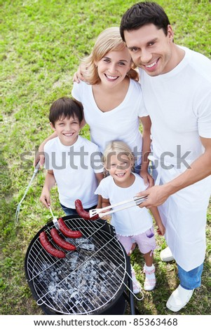 Family at barbecue outdoors - stock photo