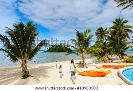 Family  at beautiful tropical beach with palm trees, white sand, turquoise ocean water and blue sky at Cook Islands, South Pacific - stock photo