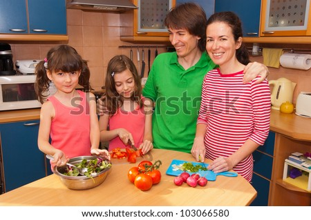Family at home cooking salad. Happy smiling parents with kids cook healthy food together at kitchen
