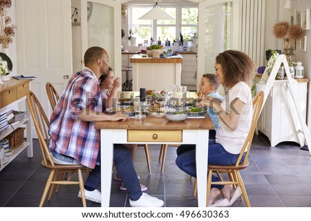 Family At Home Eating Meal In Kitchen Together